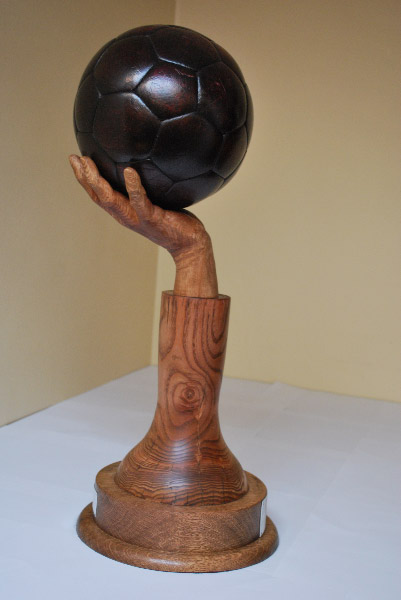 Carved wooden trophy depicting a hand holding a real leather water polo ball