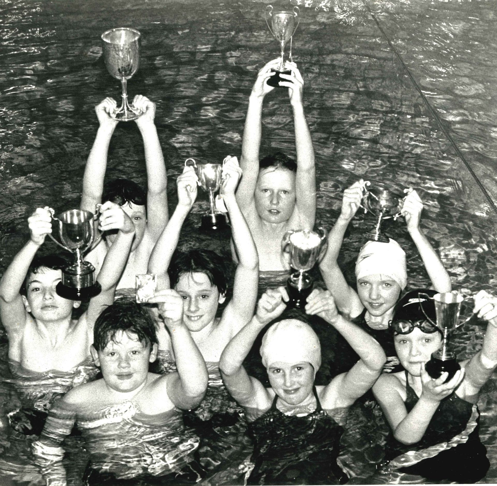 Swimmers holding trophies aloft
