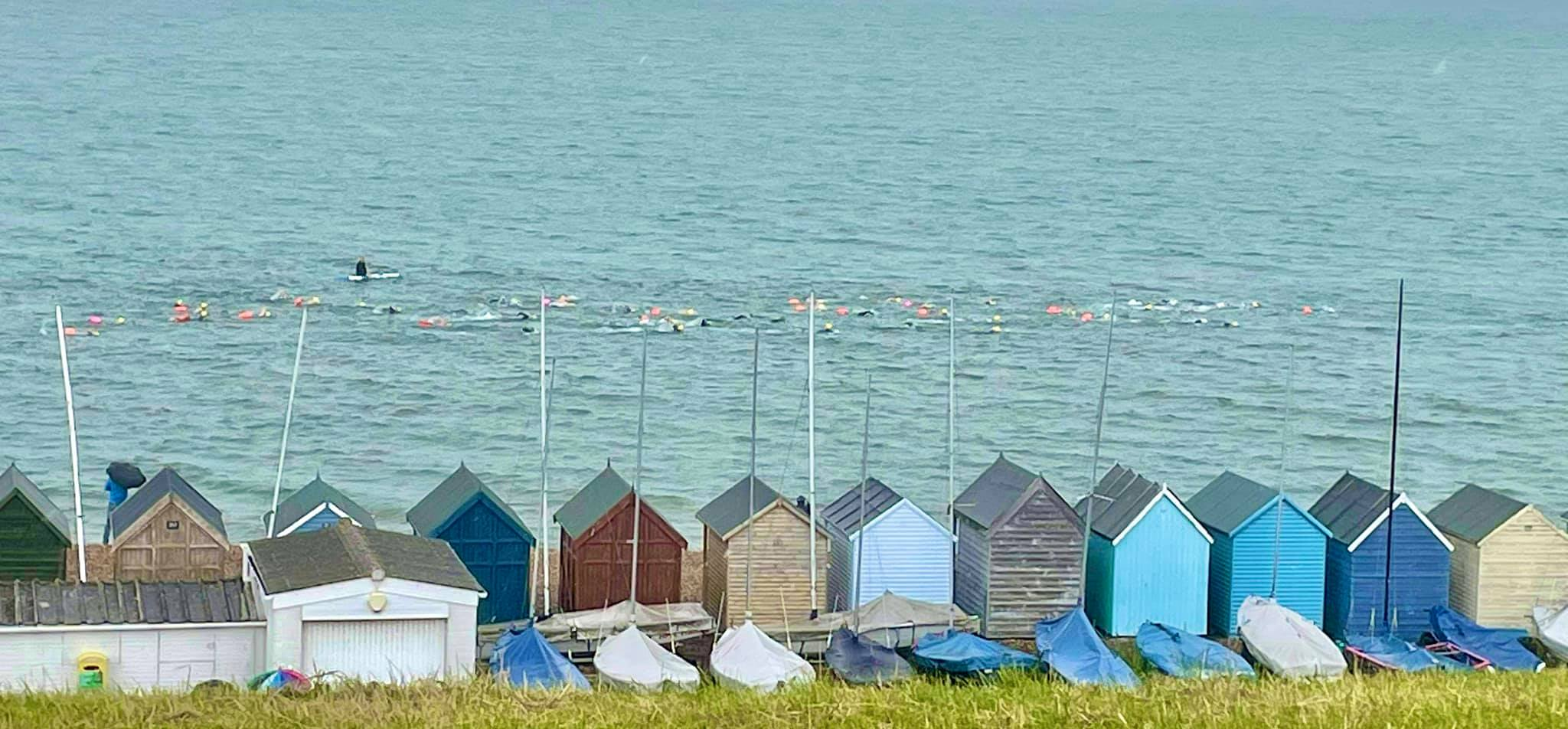 Beach huts with line of swimmers in the seas behind